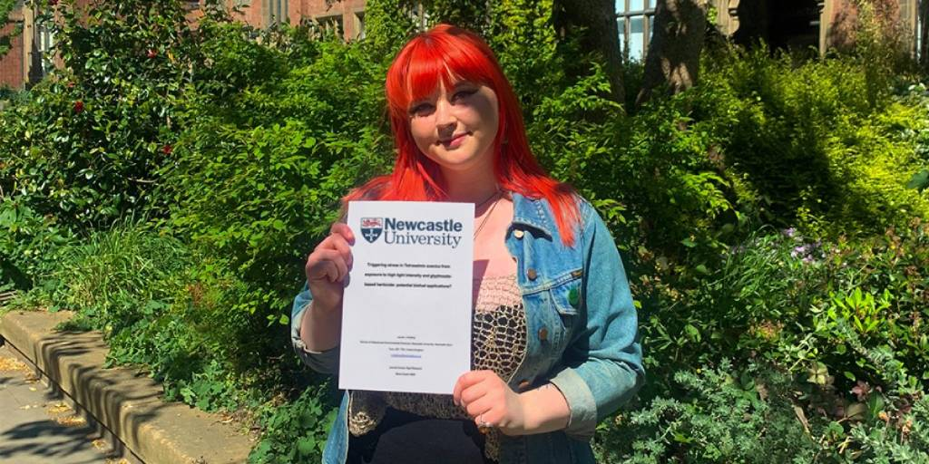 Newcastle Uni student Lauren proudly showing off her dissertation