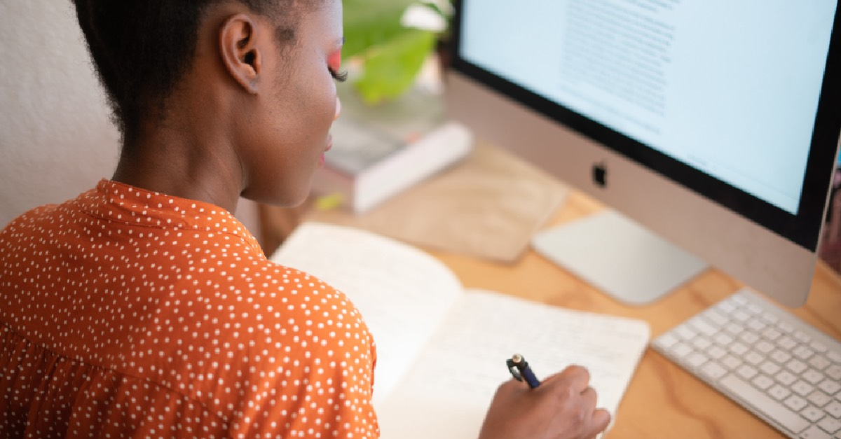 Girl in Orange Shirt Studying at Home with Notepad and Computer